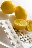 Limoni e pillole di influenza - rimedio del grippe Fotografie Stock Libere da Diritti