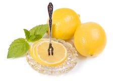 Limoni - fette e frutta sul piattino a cristallo, forcella d'annata per il le Immagini Stock Libere da Diritti