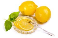Limoni - fette e frutta sul piattino a cristallo, forcella d'annata per il le Immagine Stock Libera da Diritti