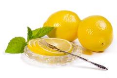 Limoni - fette e frutta sul piattino a cristallo, forcella d'annata per il le Fotografia Stock Libera da Diritti