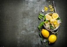 Limoni freschi in una casseruola con le foglie e la scorza Fotografia Stock