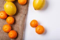Limoni gialli freschi con i mandarini arancio sulla borsa Immagini Stock