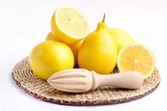 Limoni maturi freschi sullo spremitoio di legno dei limoni succosi orizzontali bianchi del fondo Fotografie Stock