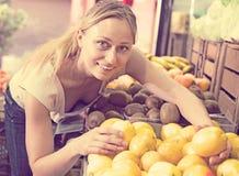 Limoni sorridenti della tenuta della donna in mani nel deposito della frutta Fotografia Stock Libera da Diritti