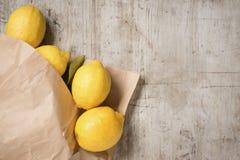 Limoni in un sacco di carta marrone contro un fondo di legno Fotografie Stock Libere da Diritti