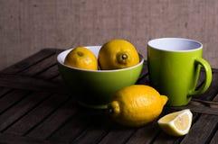 Limoni in una ciotola con una tazza di tè Fotografie Stock