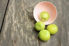 Limoni in una ciotola rosa su un fondo di legno Immagini Stock Libere da Diritti
