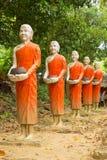 Limosnas que recorren de las estatuas de Buddha redondas Fotografía de archivo