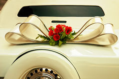 Limousine backside ornate with flowers. White wedding retro car closeup. Yellow toned. Royalty Free Stock Photography