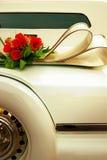 Limousine backside ornate with flowers. White wedding retro car closeup. Yellow toned. Royalty Free Stock Image