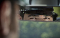 Limousine Chauffeur. A driver look on the limousine mirror Stock Photos