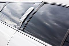 Limousine with reflection. Limousine closeup from the side with reflection of the cloudy sky in the side window Stock Photos