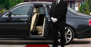 Limousinenfahrerstellung nahe bei geöffneter Autotür mit rotem Teppich lizenzfreie stockbilder