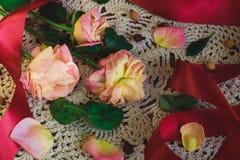 Limp τριαντάφυλλα με την κόκκινη κορδέλλα άσπρο doily δαντελλών στο εκλεκτής ποιότητας ύφος στοκ φωτογραφία με δικαίωμα ελεύθερης χρήσης