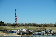 Limp American flag on flagpole over a parking lot. Lifeless United States flag on a flagpole overlooking a car park stock photography
