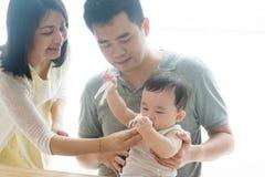 Limpa a cara do bebê com o tecido Imagens de Stock Royalty Free