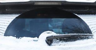 Limpador do carro no vidro traseiro coberto com a neve fotos de stock