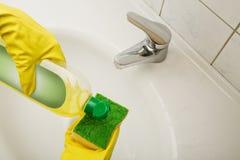 Limpando a bacia de lavagem no banheiro Fotos de Stock