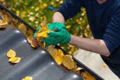 Limpando a calha da chuva durante o outono fotografia de stock