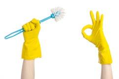 Limpando a casa e a limpeza do toalete: mão humana que guarda uma escova azul do toalete nas luvas protetoras amarelas isoladas e imagens de stock