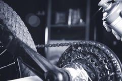 Limpando e lubrificando uma corrente e uma engrenagem da motocicleta com pulverizador do óleo/luz escura imagem de stock