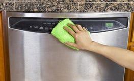 Limpando a máquina de lavar louça limpa com o pano de Microfiber Imagens de Stock