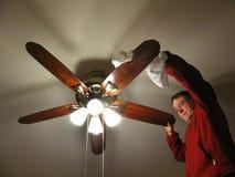 Limpando o ventilador de teto foto de stock