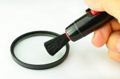 Limpando um filtro da câmera com uma ferramenta, Imagem de Stock Royalty Free