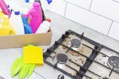 Limpando um fog?o de g?s com os utens?lios da cozinha, os conceitos do agregado familiar, ou a higiene e a limpeza imagem de stock royalty free