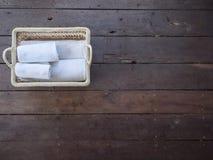 Limpe as toalhas brancas em uma cesta em um assoalho de madeira Fotos de Stock Royalty Free