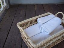 Limpe as toalhas brancas em uma cesta em um assoalho de madeira Imagem de Stock Royalty Free