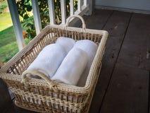Limpe as toalhas brancas em uma cesta em um de madeira e em um balcão Imagem de Stock