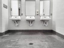 Limpe espelhos públicos simples dos dissipadores do banheiro Foto de Stock