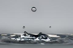 Limpe a gota da água que espirra na água desobstruída Fotos de Stock Royalty Free
