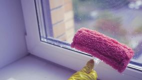Limpe a janela com um raspador em uma luva de borracha amarela Movimento lento HD, 1920x1080 video estoque