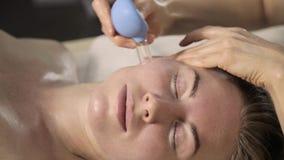 Limpe a massagem de cara, esteticista faz massagens com bancos do vácuo filme
