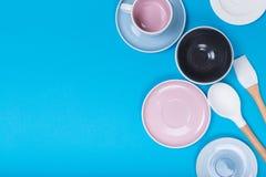 Limpe o grupo dos pratos, do caf? ou de ch? Abund?ncia de copos e de pires elegantes da porcelana no fundo azul foto de stock royalty free