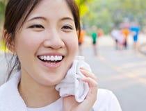 A limpeza asiática da mulher suou com uma toalha Imagens de Stock Royalty Free