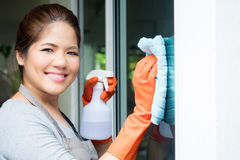 Limpeza asiática da dona de casa no vidro de janela Foto de Stock