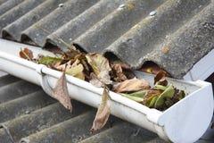 Limpeza da calha do telhado das folhas no outono Folhas e sujeira na calha da chuva Fotografia de Stock