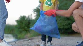 A limpeza da caridade, família nova com a criança nas luvas de borracha recolhe a recusa no saco de lixo na praia suja de video estoque