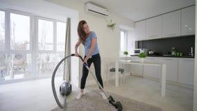 A limpeza da casa do divertimento, mulher atrativa da dona de casa que faz vácuos de limpeza e a dança alegre e canta na sala em  video estoque