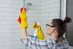 Limpeza da casa Mulher que limpa o banheiro, fêmea na roupa ocasional com o detergente e a toalha de rosto em casa no banheiro imagens de stock