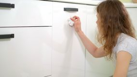 Limpeza da jovem mulher com o espanador na cozinha em casa video estoque