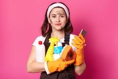 A limpeza da mulher caucasiano bonita feliz que leva os materiais, empregada da mulher com o telefone nas mãos, satisfez facial fotografia de stock