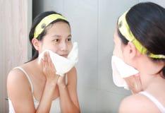 A limpeza da mulher que lava sua cara com toalha reflete com espelho do banheiro Imagens de Stock Royalty Free
