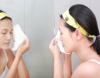 A limpeza da mulher que lava sua cara com toalha reflete com espelho do banheiro Foto de Stock Royalty Free