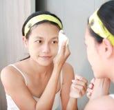 A limpeza da mulher que lava sua cara com toalha reflete com espelho do banheiro Fotografia de Stock Royalty Free