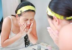 A limpeza da mulher que lava sua cara reflete com espelho do banheiro Imagem de Stock