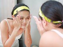 A limpeza da mulher que lava sua cara reflete com espelho do banheiro Foto de Stock